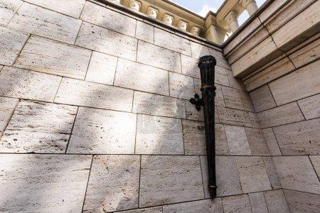 Photo pour Ancienne torche de fer sur le mur blanc en béton à l'extérieur - image libre de droit