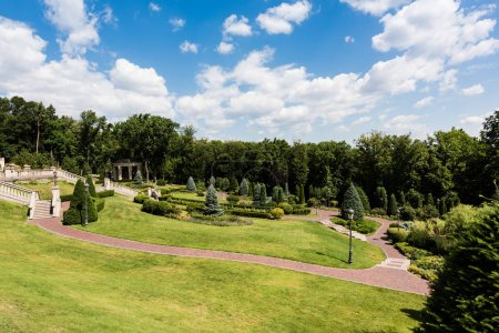 Photo pour Walkway near green grass, bushes and trees in park - image libre de droit