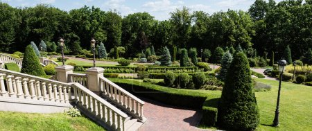 Photo pour Panoramic shot of white stairs near walkway and green trees in park - image libre de droit