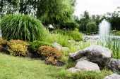 selective focus of green grass with stones near pond with fountain