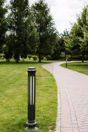 Photo pour Foyer sélectif de la lampe de plein air près de la passerelle et les arbres sur l'herbe verte - image libre de droit