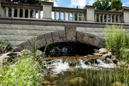 Photo for Stone bridge near steam with flowing water on rocks in park - Royalty Free Image