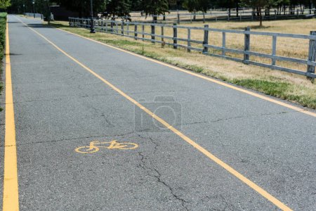 Photo for Yellow symbol of bicycle lane on grey asphalt near fence - Royalty Free Image
