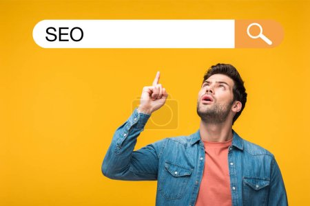 Photo pour Confused handsome man pointing with finger at search bar illustration with seo lettering isolated on yellow - image libre de droit