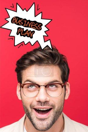 Photo pour Bel homme excité en lunettes regardant vers le haut une illustration de bulle vocale avec plan d'affaires lettré isolé sur rouge - image libre de droit