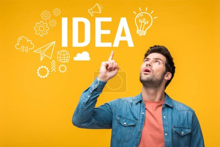 Photo for Confused handsome man pointing with finger at idea lettering isolated on yellow - Royalty Free Image