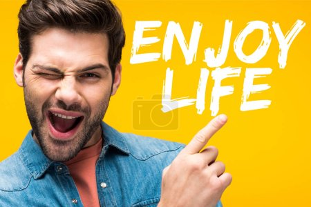 Photo pour Handsome man pointing with finger with enjoy life inspiration and winking isolated on yellow - image libre de droit