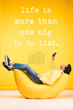 Photo pour Man relaxing on bean bag chair and using smartphone on yellow background with life is more than one big to do list illustration - image libre de droit