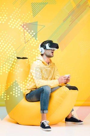 Photo pour Excité homme sur haricot sac chaise en réalité virtuelle casque sur jaune avec illustration cyberespace - image libre de droit