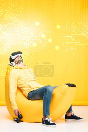 Photo pour KYIV, UKRAINE - 12 AVRIL : homme dormant sur une chaise de sac de haricots avec joystick en réalité virtuelle casque sur jaune avec illustration du cyberespace - image libre de droit