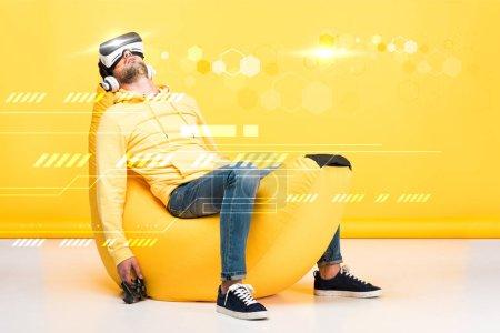 Photo pour KYIV, UKRAINE - 12 AVRIL : homme reposant sur une chaise de sac de haricots avec joystick en réalité virtuelle casque sur jaune avec illustration du cyberespace - image libre de droit