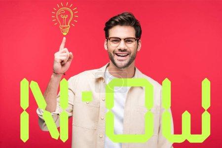Photo pour Sourire bel homme pointant du doigt l'ampoule isolée sur rouge avec maintenant lettrage - image libre de droit