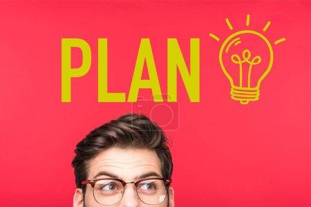 Photo pour Bel homme dans des lunettes regardant loin isolé sur rouge avec ampoule et lettrage plan - image libre de droit