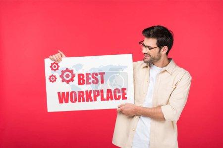 Photo pour Bel homme tenant une plaque blanche avec la meilleure illustration du lieu de travail isolée sur le rouge - image libre de droit