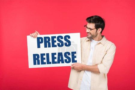 Photo pour Bel homme tenant une plaque blanche avec une illustration de communiqué de presse isolée sur du rouge - image libre de droit