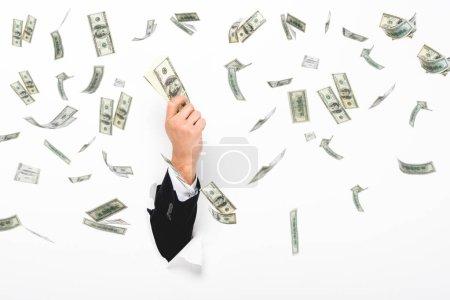 Foto de Vista cruzada del hombre que tiene dinero a través de un agujero en la pared de papel blanco sobre blanco con ilustración de lluvia de dinero. - Imagen libre de derechos