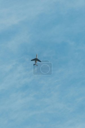 bottom view of airplane flying in blue sky