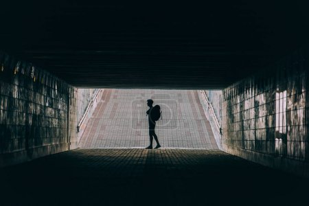Photo pour Vue latérale du jeune homme adulte avec sac à dos en tunnel - image libre de droit
