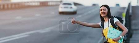 Photo pour Panoramic shot of asian woman in yellow overalls hitchhiking and holding map - image libre de droit
