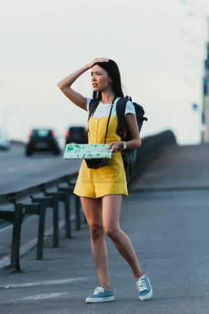 Photo pour Femme inquiète et asiatique dans les salopettes tenant la carte et regardant loin - image libre de droit