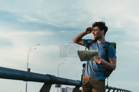 Photo for Handsome man in t-shirt and shorts holding map and looking away - Royalty Free Image