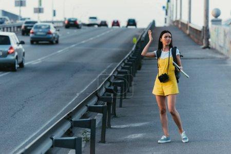 Photo pour Femme asiatique et belle dans les salopettes retenant la carte et regardant loin - image libre de droit
