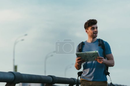 Photo pour Handsome man in t-shirt holding map and looking away - image libre de droit