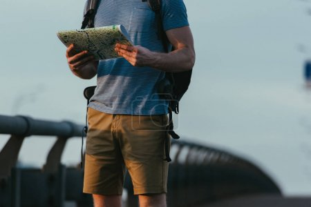 Photo pour Cropped view of man in t-shirt with backpack holding map - image libre de droit