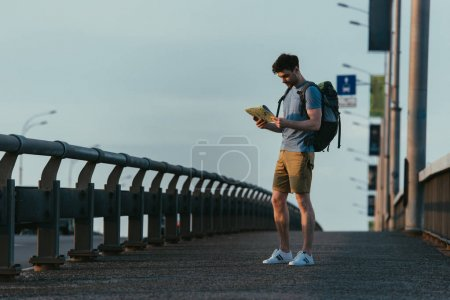 Photo for Handsome man in t-shirt and shorts looking at map - Royalty Free Image