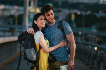 Photo pour Bel homme et asiatique femme étreignant et regardant loin - image libre de droit