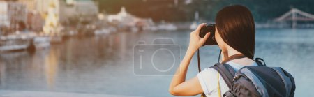Photo for Panoramic shot of brunette woman with backpack taking photo - Royalty Free Image