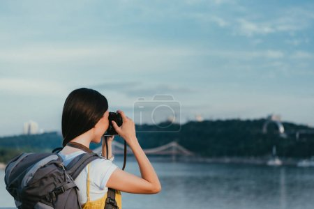 Photo for Back view of brunette woman with backpack taking photo - Royalty Free Image