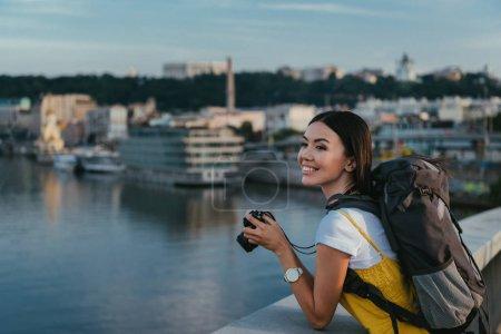 Photo pour Attrayant et asiatique femme avec sac à dos tenant appareil photo numérique - image libre de droit