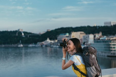 Photo for Side view of asian woman with backpack taking photo - Royalty Free Image