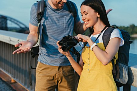 Photo for Cropped view of man and asian woman in overalls looking at digital camera - Royalty Free Image