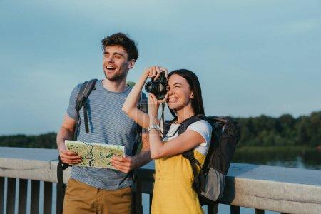Photo pour Beau homme retenant la carte et la femme asiatique dans les salopettes prenant la photo - image libre de droit