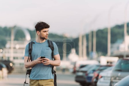 Photo for Handsome man in t-shirt holding smartphone and looking away - Royalty Free Image
