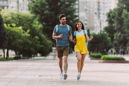 Photo for Handsome man and asian woman running and looking away - Royalty Free Image