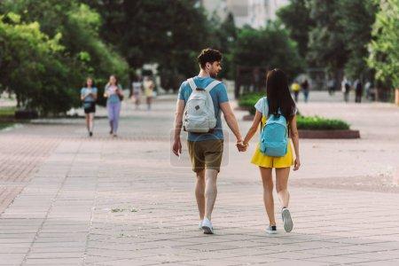 Photo pour Vue arrière de l'homme et de la femme avec des sacs à dos marchant et retenant des mains - image libre de droit