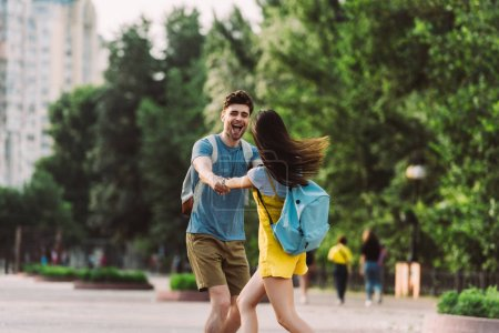 handsome man and woman with backpacks smiling and holding hands