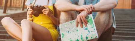 Photo pour Panoramic shot of woman holding digital camera and man holding map - image libre de droit