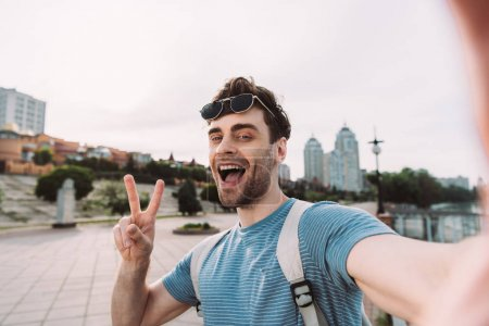 Photo pour Bel homme avec des glaces affichant le signe de paix et prenant le selfie - image libre de droit