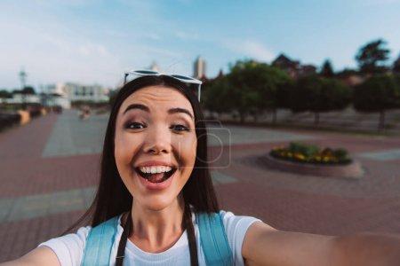 Photo pour Attrayant et asiatique femme avec des lunettes souriant et prendre selfie - image libre de droit