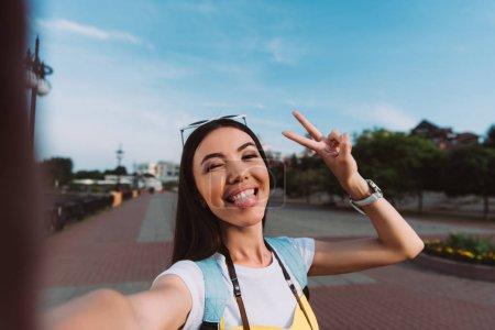 Photo pour Attrayant et asiatique femme prendre selfie et collant sur la langue - image libre de droit