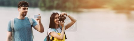 Photo for Panoramic shot of asian woman taking photo and handsome man using smartphone - Royalty Free Image