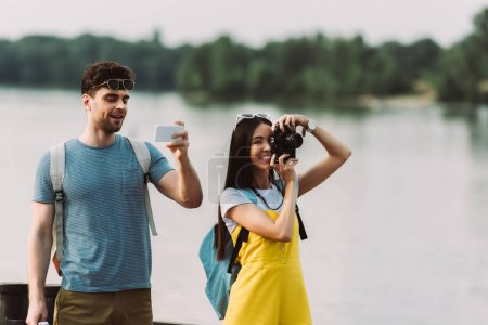 asian woman taking photo and handsome man using smartphone
