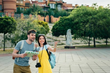 Photo for Handsome man holding map and asian woman pointing with finger - Royalty Free Image