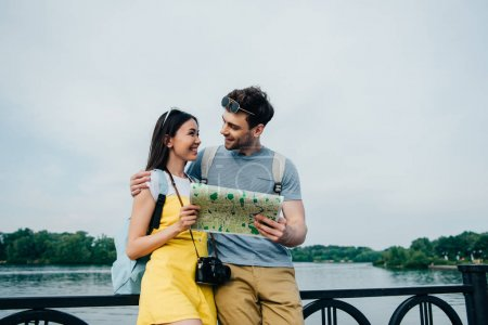 handsome man holding map and looking at asian woman