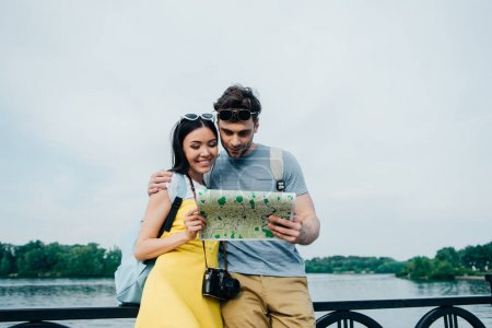 handsome man and asian woman hugging and looking at map
