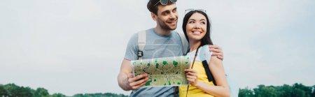 Photo pour Plan panoramique de bel homme et femme asiatique étreignant et regardant loin - image libre de droit